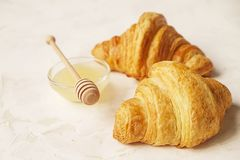 法国早餐用新鲜的新月形面包、未加工的蜂蜜和热奶咖啡 顶视图 免版税库存图片
