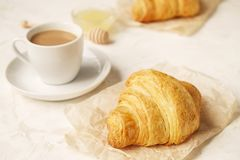 法国早餐用新鲜的新月形面包、未加工的蜂蜜和热奶咖啡 顶视图 库存图片