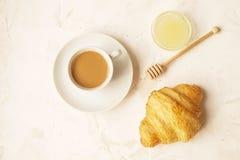 法国早餐用新鲜的新月形面包、未加工的蜂蜜和热奶咖啡 顶视图 免版税库存照片