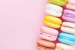 法国点心macaron或蛋白杏仁饼干在桃红色淡色背景顶视图 平的位置构成 免版税库存照片