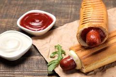 法国热狗 在委员会的鲜美在一张棕色木桌上的热狗和调味汁 便当街道食物 在小圆面包的香肠 图库摄影