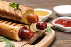 法国热狗 在委员会的鲜美在一张棕色木桌上的热狗和调味汁 便当街道食物 在小圆面包的香肠 库存照片