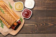 法国热狗 在委员会的鲜美在一张棕色木桌上的热狗和调味汁 便当街道食物 在小圆面包的香肠 r 库存照片