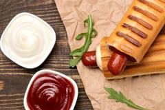 法国热狗 在委员会的鲜美在一张棕色木桌上的热狗和调味汁 便当街道食物 在小圆面包的香肠 r 免版税图库摄影