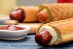 法国热狗 在委员会的鲜美在一张蓝色木桌上的热狗和调味汁 便当街道食物 在小圆面包的香肠 库存图片