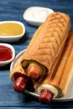 法国热狗 在委员会的鲜美在一张蓝色木桌上的热狗和调味汁 便当街道食物 在小圆面包的香肠 库存照片