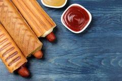 法国热狗 在委员会的鲜美在一张蓝色木桌上的热狗和调味汁 便当街道食物 在小圆面包的香肠 r 库存图片