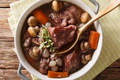 法国烹调:在酒特写镜头的红葡萄酒煮蛋公鸡在碗 Hori 库存照片