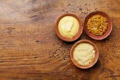法国芥末、第茂芥末和粉末在木土气桌上从上面 不同的集香料 免版税库存照片