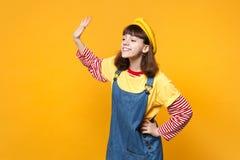 法国贝雷帽的宜人的女孩少年看在旁边,挥动和招呼用手作为通知某人隔绝了  库存照片