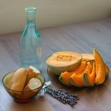 法国长方形宝石, cuted瓜,瓶在桌上的水 免版税库存图片