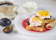 法国面包早餐与凝乳奶油、李子果酱和橙风味的在一张白色桌上 免版税库存图片