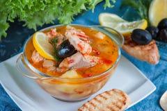 法国鱼汤法式海鲜汤用海鲜,三文鱼内圆角,虾,富有的口味,在一块白色美丽的板材的可口晚餐 库存图片
