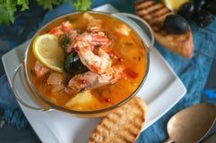 法国鱼汤法式海鲜汤用海鲜,三文鱼内圆角,虾,浓郁的味道,在美好的白色的可口晚餐 免版税库存图片
