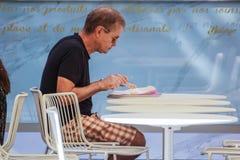 法国,尼斯2017年8月16日:一个未认出的人在游人的中心吃他的坐在一个咖啡馆的早餐 图库摄影