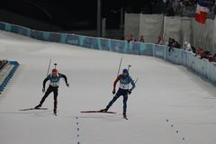 法国R的奥林匹克冠军马丁Fourcade渐近德国的西蒙Schempp赢取两项竞赛人` s 15km许多开始 库存照片
