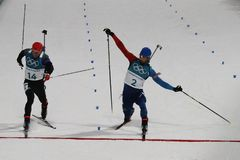 法国R的奥林匹克冠军马丁Fourcade渐近德国的西蒙Schempp赢取两项竞赛人` s 15km许多开始 免版税库存照片
