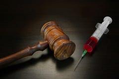 法官惊堂木和医疗射入注射器在黑木Backg 库存图片