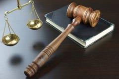 法官惊堂木,旧书,正义标度在黑表上的 免版税库存图片