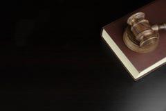 法官或拍卖人惊堂木和红色书在黑表上 库存照片