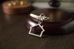 法官拍卖人锤子,在木表上的门钥匙 法院的,破产,税,抵押,拍卖,回赎权的取消概念 免版税库存照片