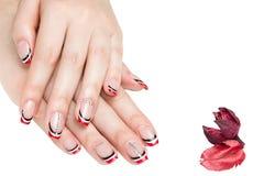 法式修剪-有红色黑白修指甲的美好的被修剪的女性手与在白色背景隔绝的假钻石 图库摄影