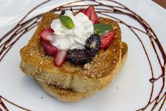 法式多士早餐服务用莓果、薄菏和奶油在巧克力装饰的白色板材 免版税库存照片