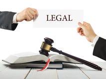 法律书籍和木法官惊堂木在桌上在法庭或执法办公室 拿着名片的律师手 免版税库存照片