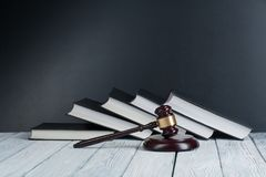 法律概念-与一根木法官惊堂木的开放法律书籍在桌上在法庭或执法办公室 库存图片