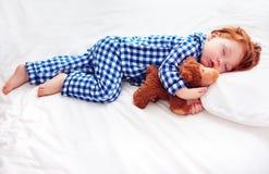 法绒睡衣的可爱的红头发人小孩婴孩睡觉与长毛绒取暖器玩具的 免版税库存照片