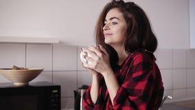 法绒衬衣饮用的茶的年轻美丽的性感的女孩和作梦关于某事,当站立在一个舒适顶楼时 股票录像