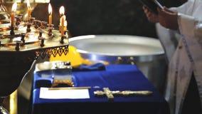 法衣的教士拿着一部圣经,在十字架前站立并且读祷告在洗礼礼拜式  影视素材
