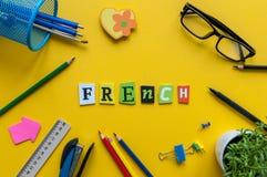 法语-用被雕刻的信件做的词在有办公室或学校用品的,文具黄色书桌 Franch的概念 免版税库存照片