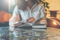 法院记录,笔记本,在桌上的日志特写镜头在咖啡馆 坐在桌和阅读书上的白色衬衣的女实业家 免版税库存图片