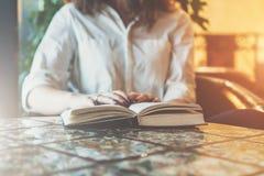 法院记录,笔记本,在桌上的日志特写镜头在咖啡馆 坐在桌和阅读书上的白色衬衣的女实业家 库存图片