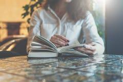 法院记录,笔记本,在桌上的日志特写镜头在咖啡馆 坐在桌和阅读书上的白色衬衣的女实业家 图库摄影
