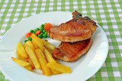 泛油煎的猪肉牛排用炸薯条。 免版税库存照片