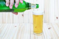 泡影和啤酒在用手是倒的啤酒的玻璃 免版税库存照片