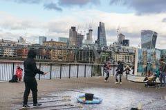 泡影在千年桥梁附近的公园和圣保罗大教堂一个人展示与孩子和父母的在伦敦 免版税库存图片