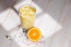泡影茶 与珍珠的自创橙色牛奶茶在木桌上 库存照片