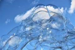 泡影起泡在蓝天的浮动肥皂漂泊与云彩 免版税图库摄影
