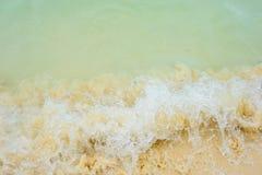 泡沫似的波浪是在黄沙的事件 海滩在一个热带天堂,休闲,放松 背景峡湾光芒海运星期日 免版税库存图片