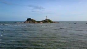 泡沫似的波浪移动从海岸到在岩石的灯塔 股票录像