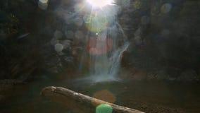 泡沫似的瀑布奔跑向在烧焦的光芒下的湖 股票录像