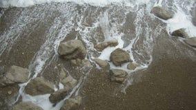 泡沫似的飞溅的海浪潮在与石头的海沙海岸挥动洗涤  影视素材