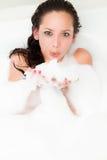 泡沫浴妇女吹的泡影在木盆的 库存照片