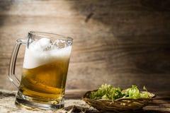 泡沫的啤酒在篮子的蛇麻草旁边从大啤酒杯溢出 库存照片