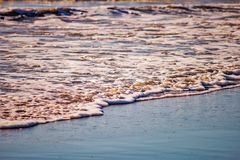 泡沫,在海滩的沙子 库存图片