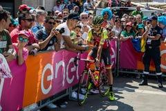 波代诺内,意大利2017年5月27日:专业骑自行车者Mets在指挥台署名附近的爱好者 库存照片