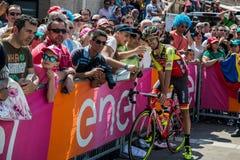 波代诺内,意大利2017年5月27日:专业骑自行车者Mets在指挥台署名附近的爱好者 图库摄影